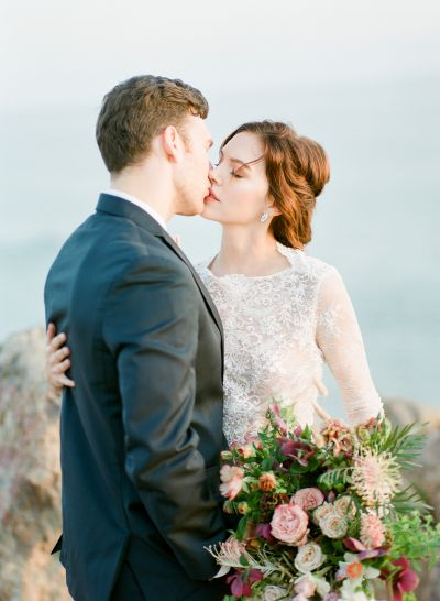 A bride kisses her groom and holds a bouquet by Lavenders Flowers